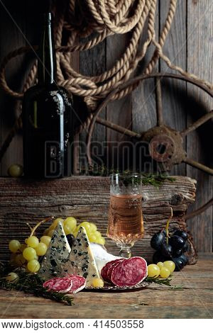 Rustic Still Life With White Wine And Snacks. On An Old Wooden Table Wine, Blue Cheese, Dry-cured Sa