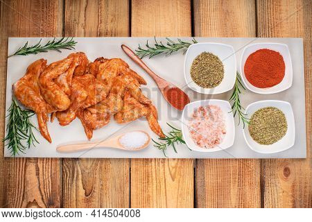 Chicken Wings Marinated In Red Sauce On A Plate On A Wooden Background With Different Spices. Raw Ch