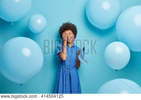 Pleased Dark Skinned Curly Woman Makes Face Palm Smiles Broadly Holds High Heel Shoes Wears Fashiona