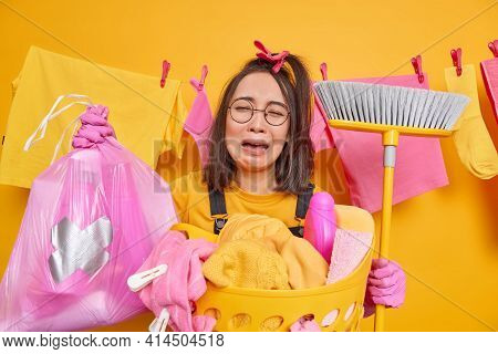 Crying Frustrated Asian Woman Holds Polythene Bag With Bottle Of Detergent Broom For Sweeping Floor