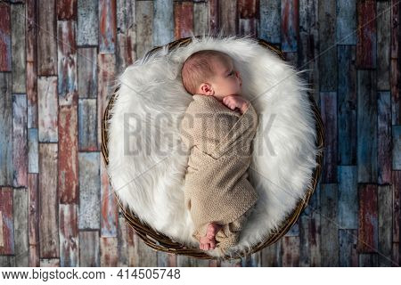 Little newborn baby sleeping in wooden basket on fluffy blanket, new youngest member of the family