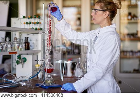 A young female scientist using an apparatus for the experiment in a working atmosphere at the university laboratory. Science, chemistry, lab, people