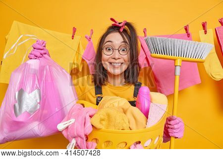 Positive Asian Woman Holds Broom For Sweeping Floor Poses With Cleaning Supplies Polythene Bag Full