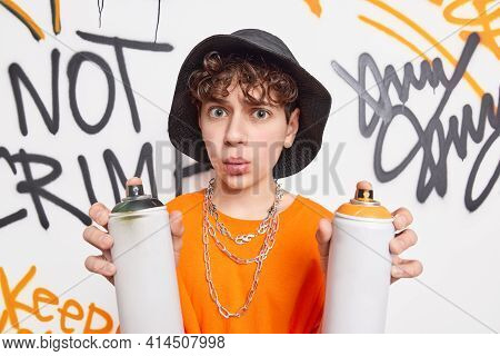 Urban Style. Surprised Creeative Teenage Boy Disrupts Street Walls Holds Two Aerosol Sprays Makes Gr