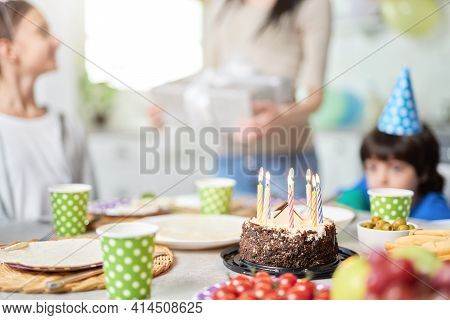 Close Up Of A Birtday Cake With Candles On The Table. Happy Latin American Family With Children Cele