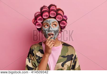 Portrait Of Surprised Housewife Applies Clay Mask On Face Looks Wondered Above Makes Hairstyle With