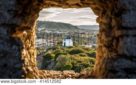 Old Windmill Through Small Window In Obidos Fortress Wall, Portugal. Evening Sunlight
