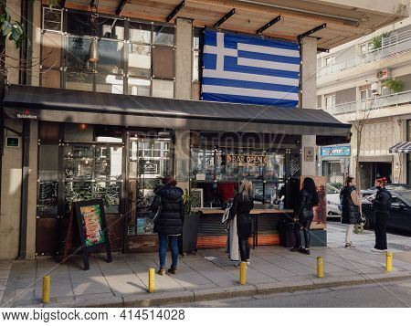 Thessaloniki, Greece - March 27 2021: Customers Outside Take-away Working Bar Due To Covid-19 Restri