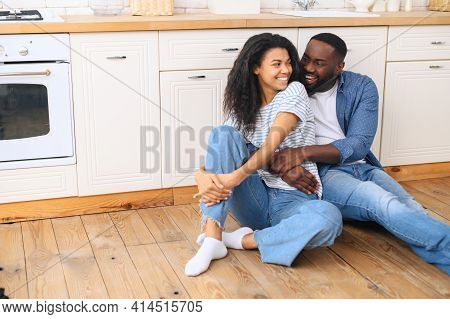 Married Couple Sitting On Warm Wooden Floor In Modern Kitchen, Hugging Looking At Each Other, Family
