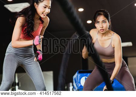 Strong Athlete Exercising With Battle Ropes At The Fitness Gym With Female Trainer.  Women Good Shap