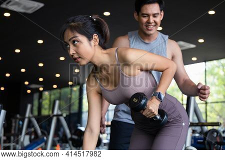 The Personal Trainer Helps Asian Women With One Arm Triceps Workout In Fitness Gym. Concepts Of Exer