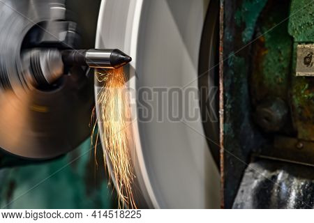 Grinding A Shaft With Sparks With An Abrasive Wheel On A Grinding Machine.