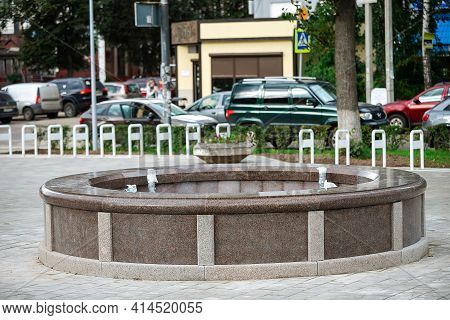 The Fountain In The Park Is Not Working. Drained Bowl Of A Granite Fountain. Not The Tourist Season.