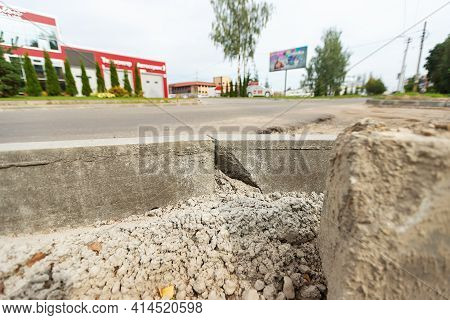Broken Curb Along The Road. Repair Work Of The Sidewalk. Cement Slabs In Cracks And Low-quality Mate