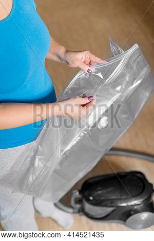 A Woman Opens A Vacuum Bag For Storing And Transporting Clothes. Vacuum Packing Of Things Using A Va