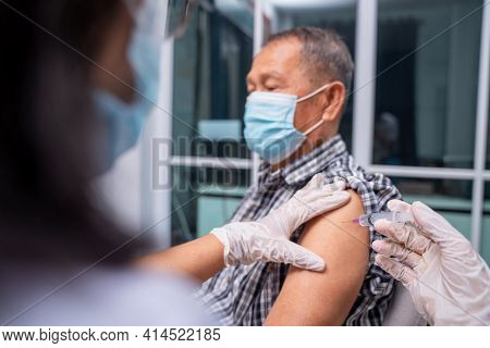 Doctor Making A Vaccination In The Shoulder Of Old Patient, Flu Vaccination Injection On Arm, Corona