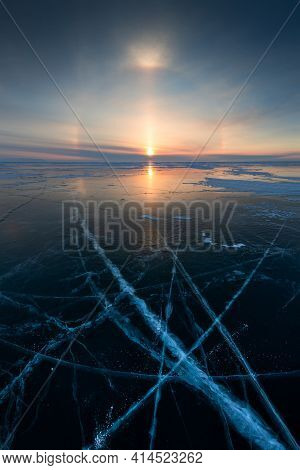 Baikal Lake In Winter With Transparent Cracked Blue Ice. Solar Halo Effect At Sunrise. Baikal, Siber