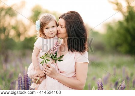 Happy Family Outdoor. Middle-aged Mother Hugs Her Daughter In Field. Mother's Day.