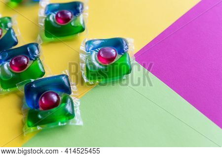 Capsules For Washing With Green, Blue And Re Gel On Colorful Background. Liquid Laundry Detergent Po