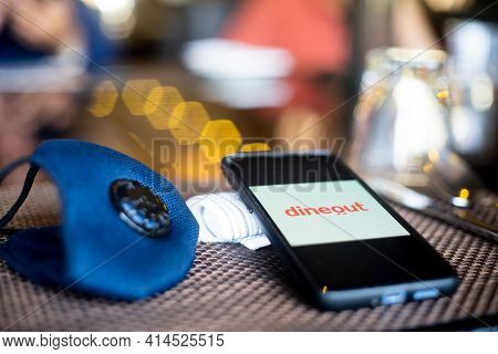 Blue Cloth Mask With Mobile Phone At Side With A Zomato Dineout In Restaurant Showing The Popularity