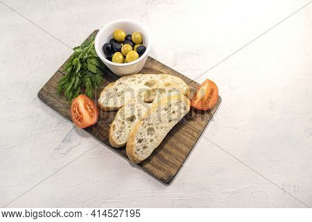 Sliced Bread On Serving Board Served With Olives, Tomatoes, And Fresh Herbs On White Table. Fresh, T