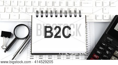White Notebook With Text B2c On The White Keyboard With Calculator,magnifier And Pen