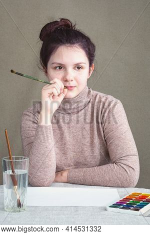 A Teenage Girl Sitting At Home At The Table, In Front Of Her A White Sheet Of Paper, Watercolor Pain