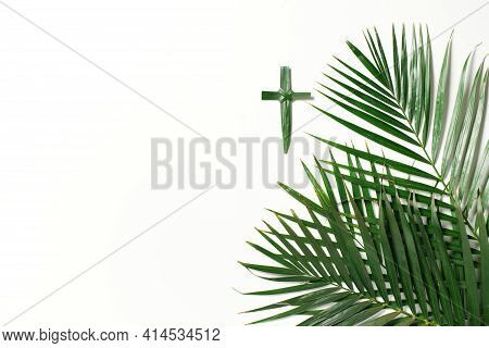 Palm Sunday Concept. Cross Made Of Palm And Tropical Leaves Isolated On White Background. Christian