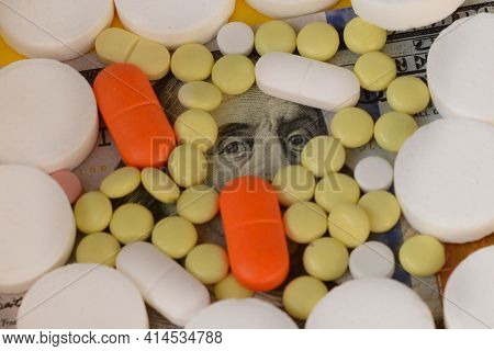 Hundred Dollar Bill Covered With Colorful Medical Pills. Money, Healthcare, Drug Trafficking Concept