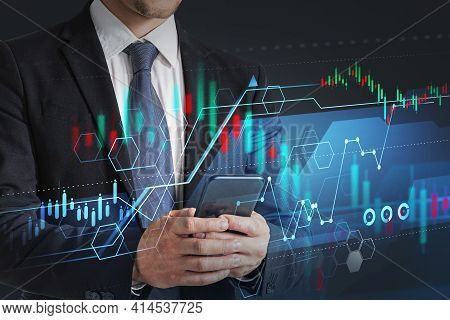 Businessman Wearing Formal Suit Is Holding The Smart Phone. Forex Candlestick, Graph, Pie Diagram An