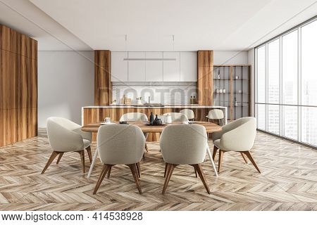 Open Space Eating Room Interior With Parquet Floor And Table With Chairs, White Wooden Kitchen Set.