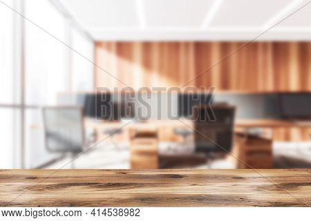 Wooden Desk On Foreground, Background Of Blurred Wooden Office Consulting Room With Table And Deskto