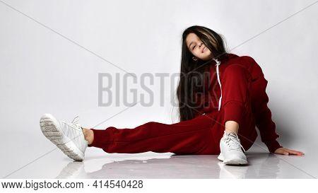 Joyful Teenage Girl, Imposingly Sprawled On The Floor Of The Studio, Posing In A Warm Comfortable Ov