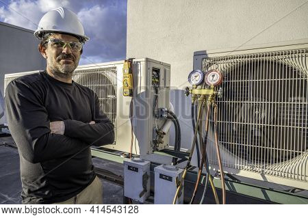 Hvac Technician Standing Next To Mini Splits With Tools On Them