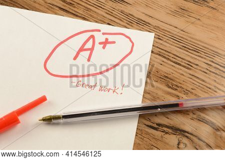 A Graded School Paper Marked In Red Ink Over A Wood Desktop.