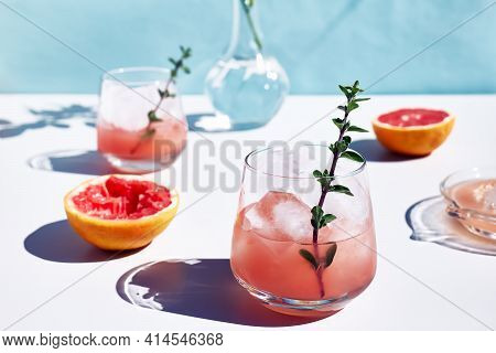 Summer Grapefruit Cocktail. Fresh Healthy Grapefruit Beverage With Herbs On Sunlight With Hard Shado