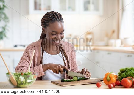 Happy Young Black Woman Cooking Fresh Vegetable Salad In Kitchen, Chopping Cucumber