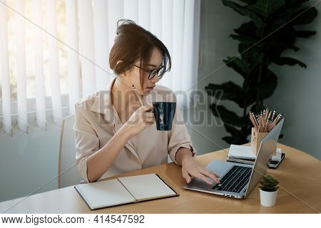 Portrait Of Beautiful Accountant Sitting At Desk With Interior Drinking Hot Beverage Holding Cup Wit
