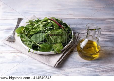 Plate With Fresh Leafy Greens, Bottle Of Olive Oil And Fork On White Wooden Table, Vegetarian Food,