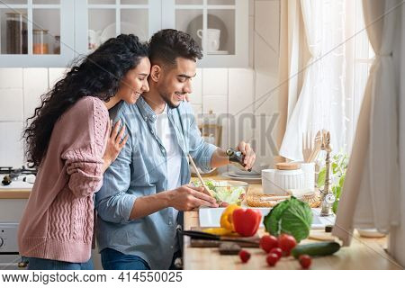 Modern Muslim Couple Cooking Healthy Food In Kitchen At Home Together