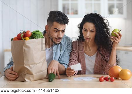 Frustrated Arab Spouses Sitting In Kitchen Checking Bills After Grocery Shopping