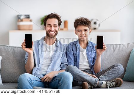 We Like This App. Happy Father And Son Showing Their Smartphones With Blank Black Screens, Sitting O