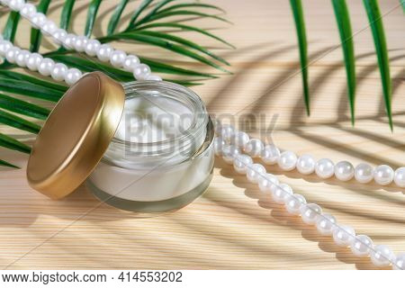 Anti-wrinkle Moisturizing Face Cream In An Open Jar And Pearl Beads On A Wooden Desk. Green Leaf Cas