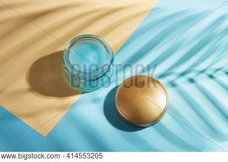 Moisturizing Face Gel In An Open Jar And Golden Lid Against Blue Yellow Paper Background. Plant Leaf