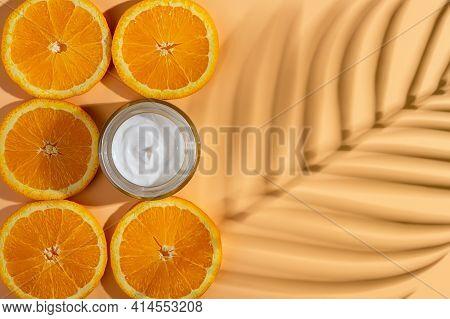 Anti-wrinkle Moisturizing Face Cream And Juicy Orange Slices Near Blank Surface With Palm Leaf Shado