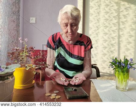 Senior Woman Sitting On Window Sill With Purse With Pills