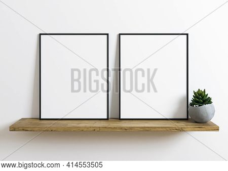 Double Black Frame Mockup On Wooden Shelf With Green Plant And White Wall Behind It. Empty Poster Tw