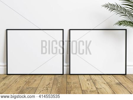 Double Black Frame Mockup On Wooden Floor With Green Plant And White Wall Behind It. Empty Poster Tw