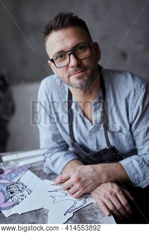 Bearded Middle Aged Male Artist In Glasses Sitting On A Background Of Workplace. Linocut Master In A