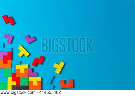 Different Colorful Shapes Wooden Puzzle Blocks On Light Blue Background. Geometric Shapes In Differe